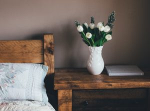 Wooden bedframe with a vase on the bedside table