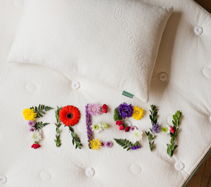 Green avocado mattress with a fresh flower arrangement.